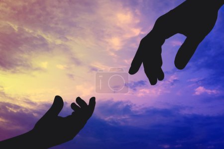 Silhouettes of father and child hands reaching to ...