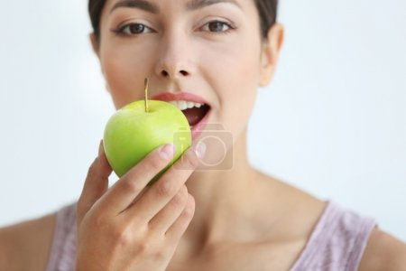 Young woman eating green apple, close up
