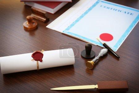 Photo pour Rouleau attaché avec vieux sceau de cire notarié et timbre sur la table - image libre de droit
