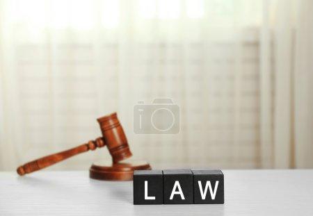 Photo pour Cubes noirs avec mot LAW et marteau sur table blanche - image libre de droit