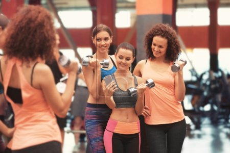 Group of young sportive women taking selfie near mirror in gym