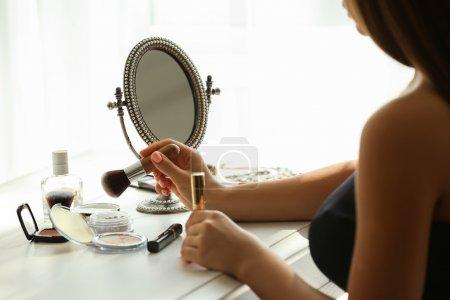 Photo pour Belle jeune femme regardant dans le miroir tout en se maquiller - image libre de droit