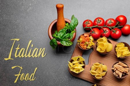 Bowls with different pasta on wooden cutting board. Text ITALIAN FOOD on gray background. Traditional meal concept.