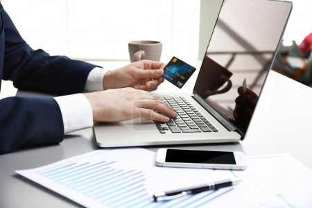 Businessman working with credit card and laptop in office