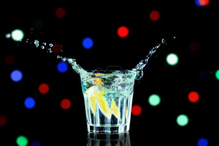 Colorful cocktail with splash on blurred lights background