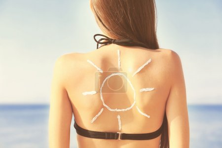 Woman with sunscreen in sun shape on back. Skin care concept.