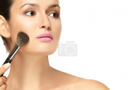 Beautiful girl applying cosmetics on white background