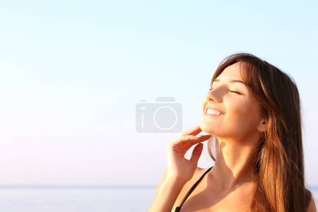Young woman sunbathing on the sea background