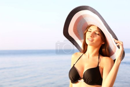 Young woman in hat sunbathing on the sea background