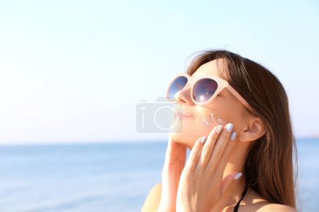 Young woman using sunscreen on the sea background