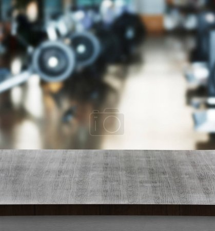 Wooden table against blurred gym interior background. Sport and healthcare concept.