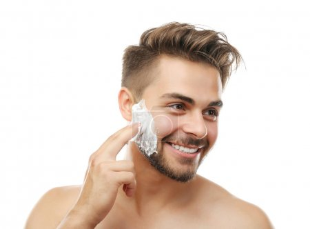 Young man applying shaving foam isolated on white