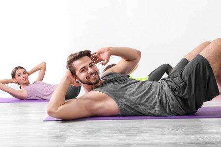 Photo pour Groupe de personnes faisant des exercices de yoga dans la salle de gym - image libre de droit