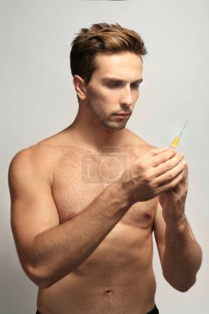 Muscular man holding syringe on white background