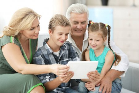 Grandparents with grandchildren with tablet
