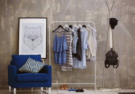 Photo pour Des vêtements à la mode suspendus sur un rack dans un dressing moderne - image libre de droit