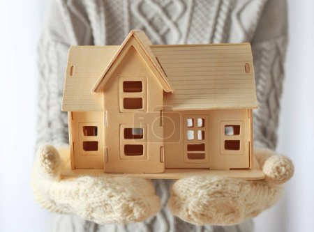 Female hands in mittens holding plywood toy house
