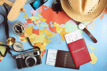 Traveller's accessories on world map background, top view. Travel planning concept