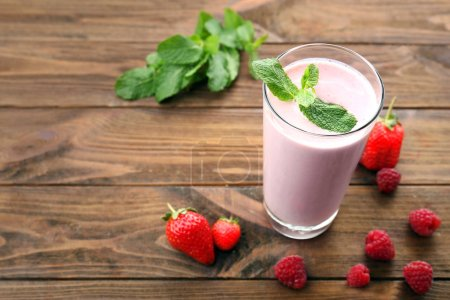 Glass of berry milk shake on wooden background