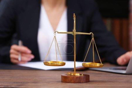 Photo pour Échelles de la justice sur la table en bois et avocate sur fond - image libre de droit