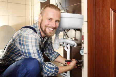 Handsome plumber repairing
