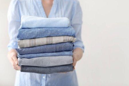 Photo pour Femme tenant pile de vêtements, gros plan - image libre de droit