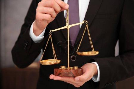 Photo pour Mains d'un avocat tenant une balance judiciaire, gros plan - image libre de droit