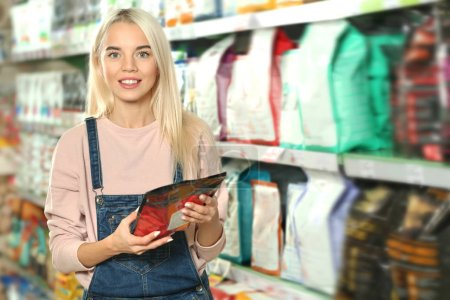Photo for Pretty young woman selecting animal food in pet shop - Royalty Free Image