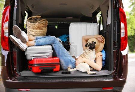 Photo pour Dormir fille dans le coffre de la voiture avec carlin mignon et bagages. Concept de voyage - image libre de droit
