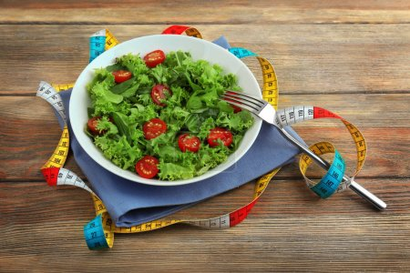 Photo for Fresh salad and measuring tape on wooden  background - Royalty Free Image