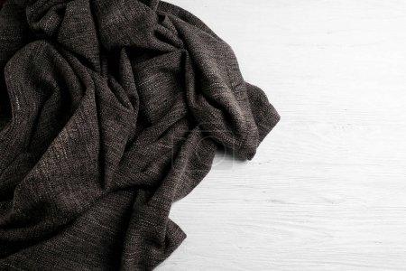 Photo pour Tissu tricoté gris sur fond bois blanc - image libre de droit