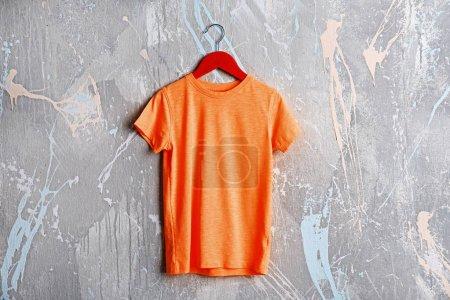 orange t-shirt against grunge wall