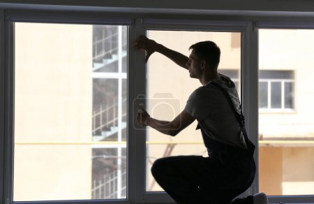 Photo for Construction worker installing window in house - Royalty Free Image