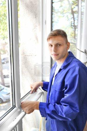 worker putting sealing foam tape on window