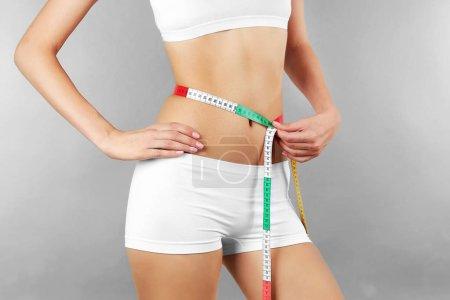 Photo pour Femme mesurant sa taille sur fond de couleur - image libre de droit