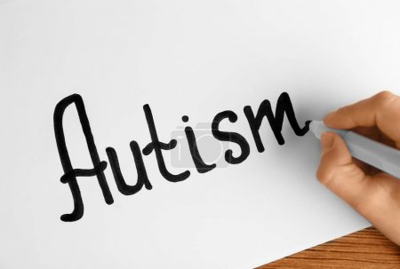 Human hand writing word AUTISM