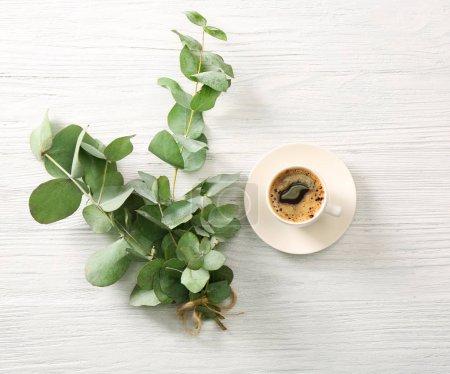 Photo pour Branches d'eucalyptus vert avec tasse de café sur la table - image libre de droit