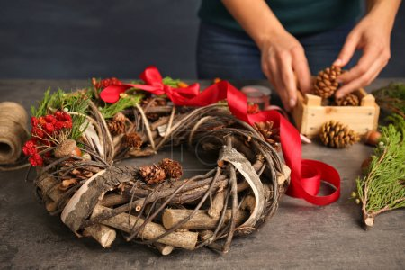 Female hands making decorative wreath