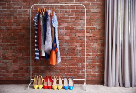 Photo for Hangers with different female clothes on brick wall background - Royalty Free Image