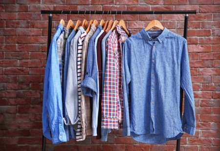 Photo for Hangers with different male clothes on brick wall background - Royalty Free Image