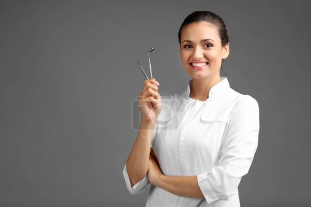 Female dentist with tools on grey background...