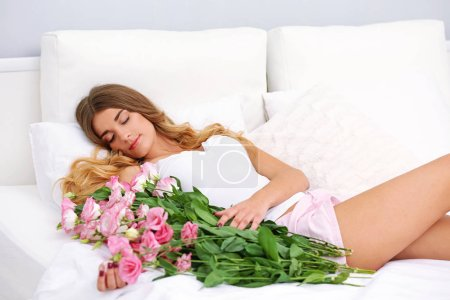 Pretty girl lying in bed with big bouquet