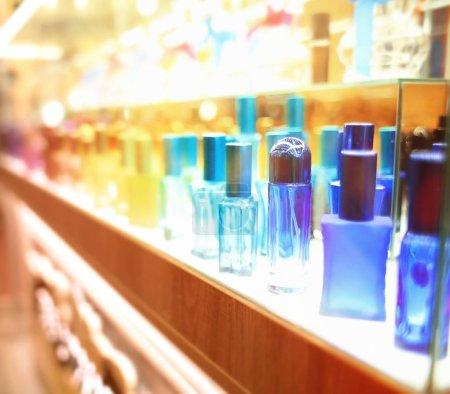 Photo pour Stand avec des bouteilles de verre coloré dans le magasin de cosmétique - image libre de droit