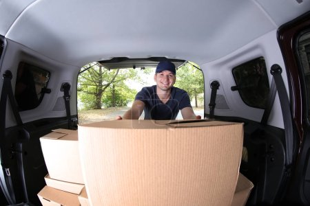 Photo for Young male deliverer loading boxes into car - Royalty Free Image