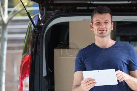 Male deliverer with tablet beside car