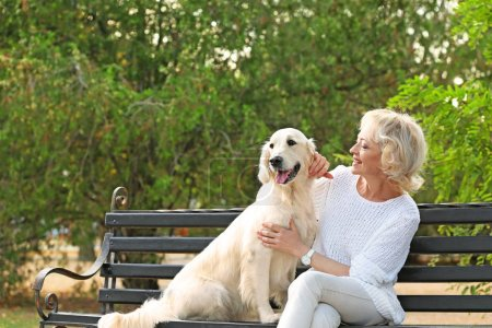 Photo for Senior woman sitting on bench with dog - Royalty Free Image