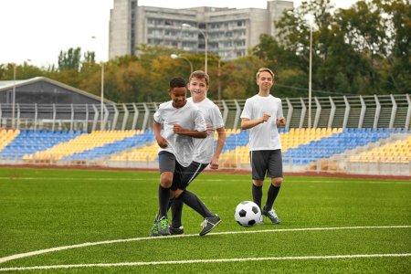Photo pour Garçons jouant au football au stade - image libre de droit
