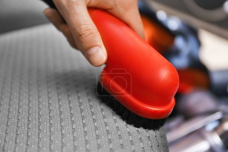 male hand cleaning car with brush