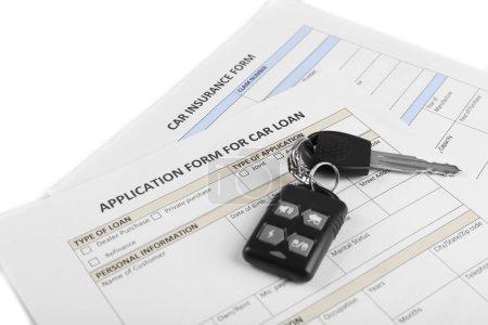 Car key on blank of insurance closeup