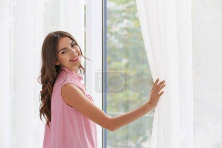Photo pour Belle femme ouvrant rideaux dans la chambre - image libre de droit
